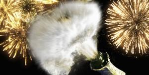 Una botella de champagne abriéndose y fuegos artificiales